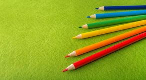 Six multicolored pencils on a green felt background. Different colored pencils with space for text. Back to school. Art lessons. Stationery stock photos