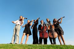 Six musicians play violins against sky Royalty Free Stock Image
