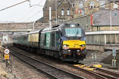 Six Nations Welsh Rugby Supporters Train Carnforth. Class 68 diesel locomotive hauling a charter train from Edinburgh to Carmarthen on 16th February 2015 passes Royalty Free Stock Photos
