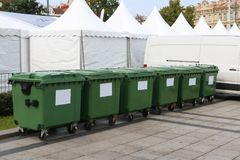 Six new plastic green garbage containers. Back side of the city. Six new plastic green garbage standard containers. Back side of the city sports festival. In the Stock Image