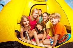 Six nice kids looking from camping tent royalty free stock photo