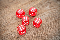 Six numbers on faces of five red dices on floor. Six numbers on faces of five red dices on wooden floor Royalty Free Stock Photos