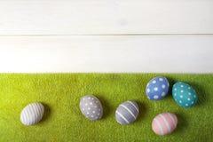 Six oeufs de pâques faits main colorés se trouvent sur une pelouse verte sur un fond en bois blanc style plat de configuration Photo libre de droits