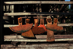 Six old hoes. Front view lying on wooden rails Stock Image