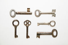 Six old keys to the safe on a white background Stock Images
