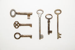 Six old keys to the safe on a white background Royalty Free Stock Photo