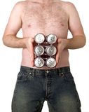 Six pack?. This image shows a young man holding a six pack of beer over his belly stock images