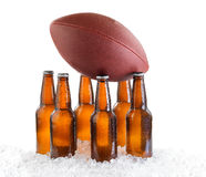 Six pack of ice cold bottled beer with American football isolate. Six pack of bottled beer holding up American Football isolated on white background Royalty Free Stock Photos