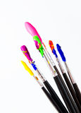 Six paint brushes with gouache  on white Stock Photography