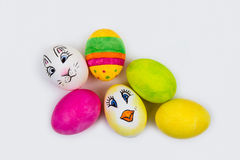 Six painted Easter eggs on a white background. Six painted Easter eggs, one yellow, one green, one pink, one multicolored, one with an Easter bunny and one with Royalty Free Stock Photography