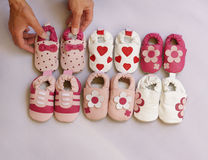 Six pairs of baby shoes on display. Hands organising six pairs of baby shoes into two lines Stock Photos