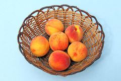 Six peaches in wicker basket Stock Photography