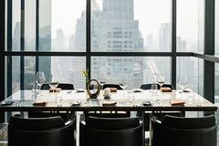 Six people dinner table with plates, knives, forks, wine glasses, glasses and napkins on marble table top with Bangkok cityscape. Six people dinner table with royalty free stock photos