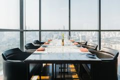 Six people dinner table with plates, knives, forks, wine glasses, glasses and napkins on marble table top with Bangkok cityscape. Six people dinner table with stock image