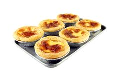 Six piece golden egg tart in foil paper cup on old rectangle aluminum baking tray for small oven isolated on white background. Closeup six piece golden egg tart stock image