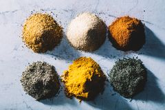 Six piles of colorful spices and herbs. Royalty Free Stock Images