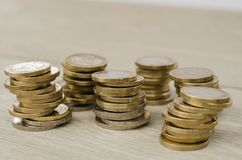 Pile of 1 Euro coins. Six piles of 1 euro coins on wooden floor in studio royalty free stock photos