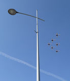 Six planes fly above the street lamp Stock Photography