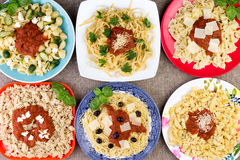 Six plats de pâtes avec de la sauce et des herbes Image stock