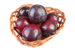 Six plums wicker basket isolated Stock Photos