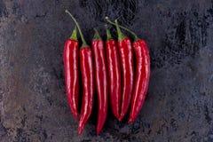 Six poivrons de piment sur le fond rouillé en métal Image libre de droits