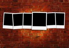 Six polaroïds vides sur le mur de briques rouge Images stock