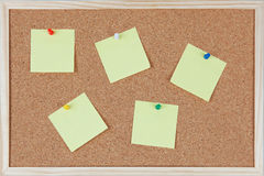 Six post-it notes with pins sticked on corkboard Royalty Free Stock Image