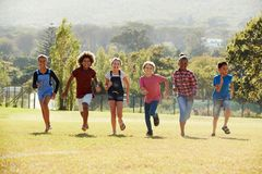 Six pre-teen friends running in a park, front view Royalty Free Stock Images
