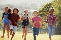 Six pre-teen friends running in a park, front view, close up Stock Photos