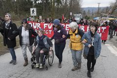 Protesters at the Kinder Morgan tank farm in Burnaby, BC. The six protesters shown oppose pipeline expansion and have agreed to be arrested and are approaching royalty free stock images