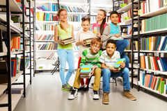 Six pupils in library with piles of books Royalty Free Stock Photography