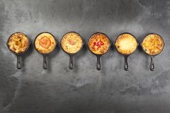 Six quiche pies in pans. Six individual mini quiche pies in cast iron pans on a dark slate effect surface stock photo