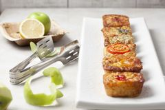 Six quiches on a white plate. A white rectangular plate with six freshly baked individual mini quiches with a pair on tongs, apple peel and lemon stock photos