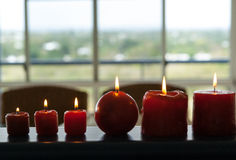 Six red candles burning. With window behind and copyspace Stock Images