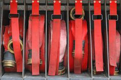 Six red hoses of firefighters in order inside the fire truck Stock Photo
