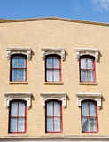 Six Red Windows in Old Brown Brick Building Stock Photography