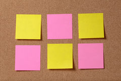 Six reminder sticky notes on cork board Royalty Free Stock Images