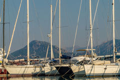 Six sailboats in a harbor. Six small white sailboats without sails in a harbor. Sky is clear and two mountain tops are seen in a haze. Photo was taken in a Stock Photos