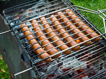 Six sausages on the grill over the coals Stock Photos