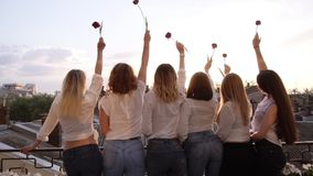 Six seductive young women are standing on a terrace in a row from their back. Wearing casual clothes, white shirts and stock video footage
