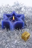 Six sided Christmas candle. A deep blue six sided christams candle nestled in silver tinsel with gold giftbox Stock Photos
