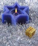 Six sided Christmas candle. A deep blue six sided christmas candle nested in silver tinsel with gold giftbox Stock Image