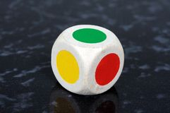 Six sided dice. Standard six sided die with coloured spots against a grey background Stock Photography