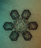 A six sided real snowflake in white background. A photomicrograph of a six sided naturally occuring single snow crystal (snowflake) in white background.  The Stock Photo