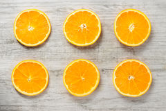 Six slices of fresh oranges on white wood background Royalty Free Stock Photos