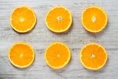 Six slices of fresh oranges on white wood background Royalty Free Stock Photo