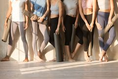 Sporty women hold yoga mats standing in row indoors stock photos