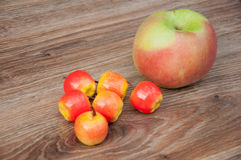 Six small apples and one big on table. Stock Photo