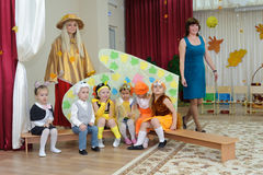Six small children dressed in carnival costumes and women. BALASHIKHA, RUSSIA - OCTOBER 26: Six small children, dressed in carnival costumes, and two adult women Royalty Free Stock Photography