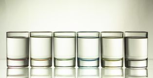 Six small multi-colored glasses on a bright background. Close up royalty free stock photo